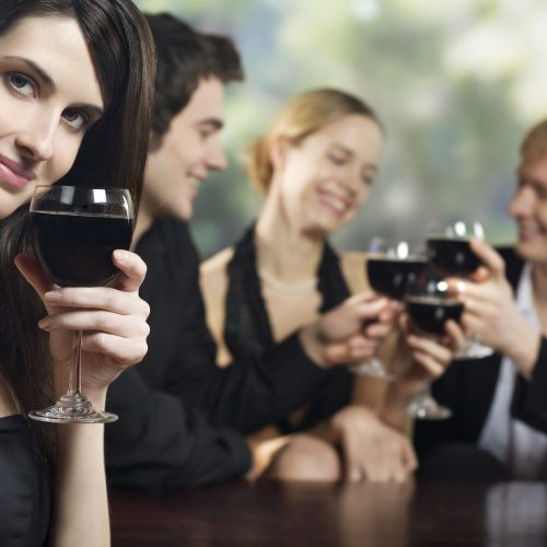 Two young couples with red-wine glasses at celebration or party